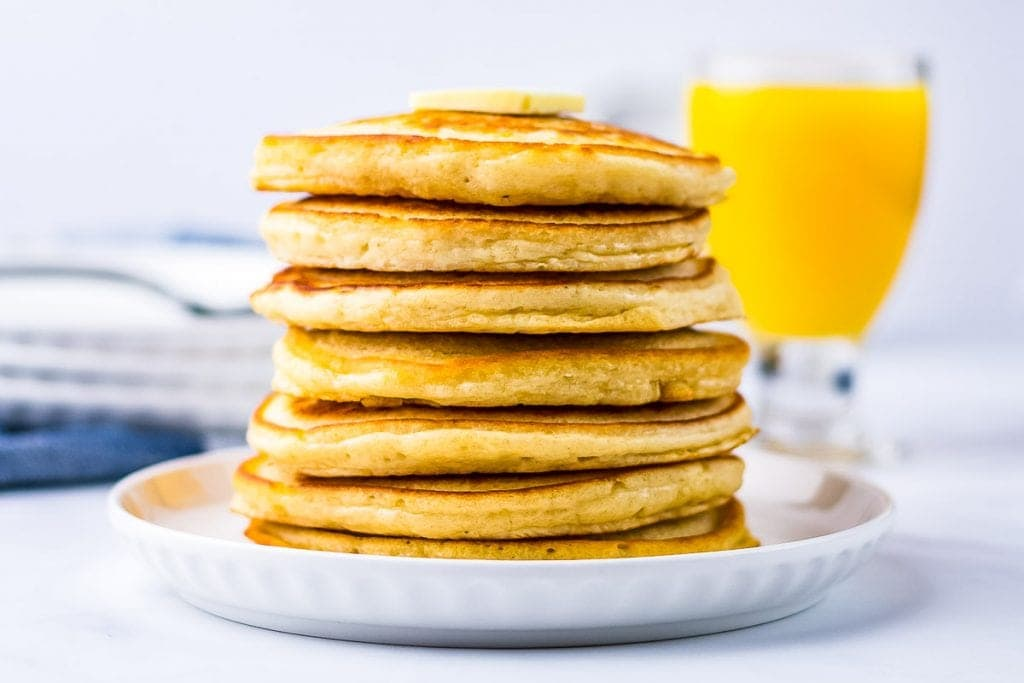 White plate with stack of pancake orange juice glass in background