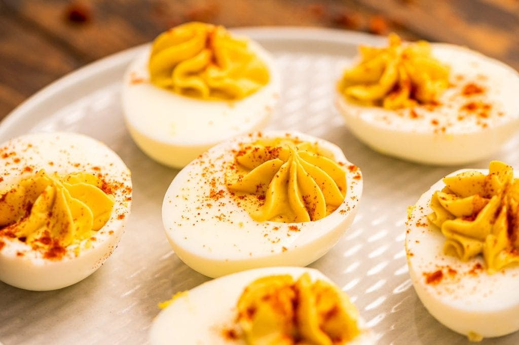 Hard boiled eggs sliced in half with deviled egg filling piped into them and garnish with paprika on plate