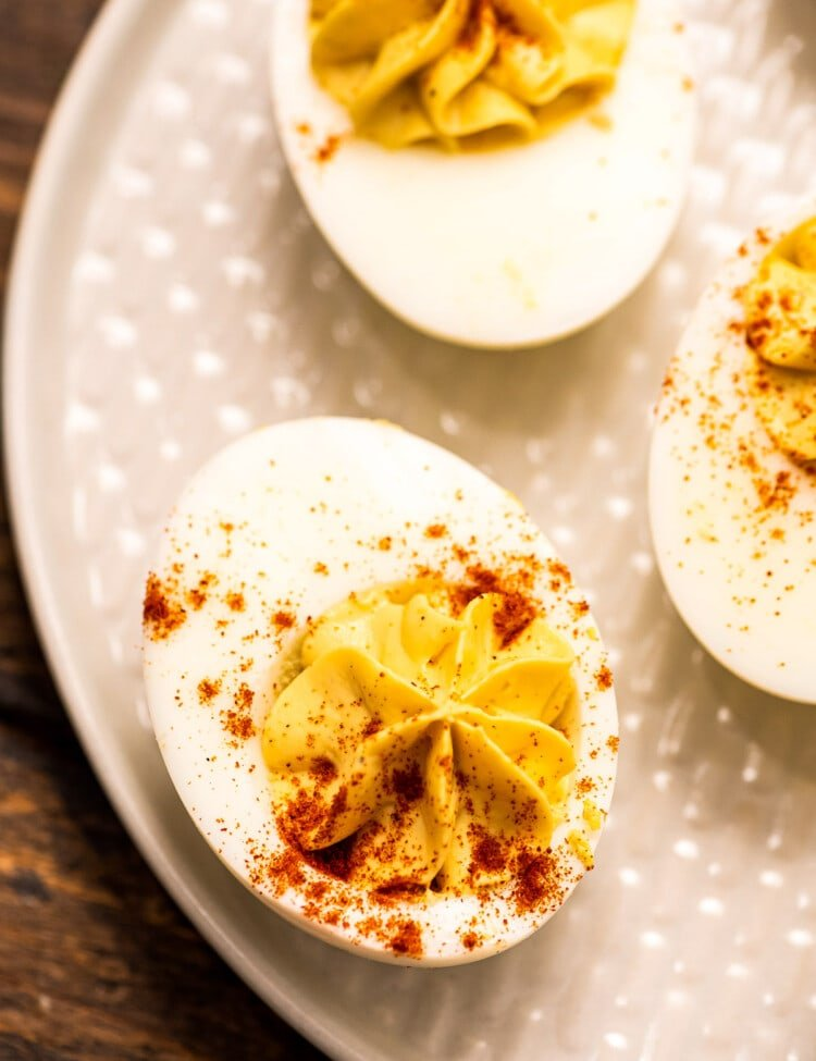 Overhead image of off white plate with deviled eggs garnished with paprika on it
