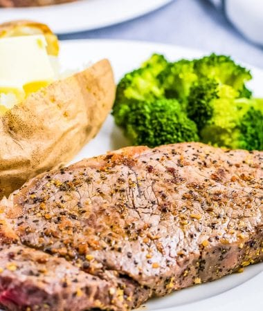 Plate with seasoned steak on it with steamed broccoli and baked potato