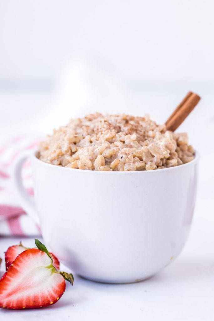 Bowl of rice pudding with cinnamon stick in it and strawberry next to bowl