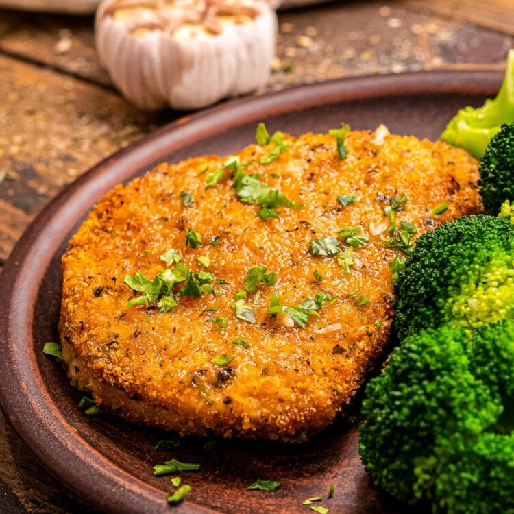 Plate with breaded pork chops and broccoli on it