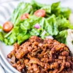 White plate with baked beans, salad on light background