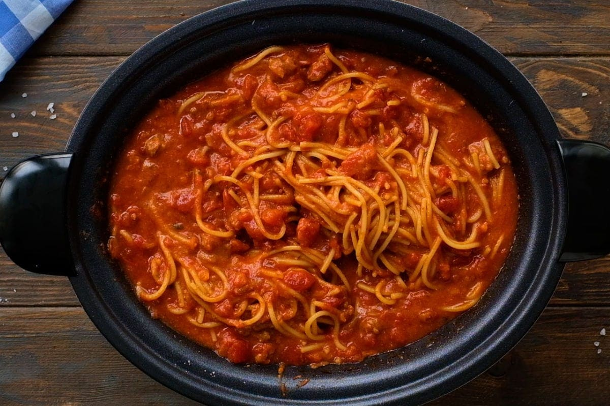 Overhead image of spaghetti in crock pot on wooden background