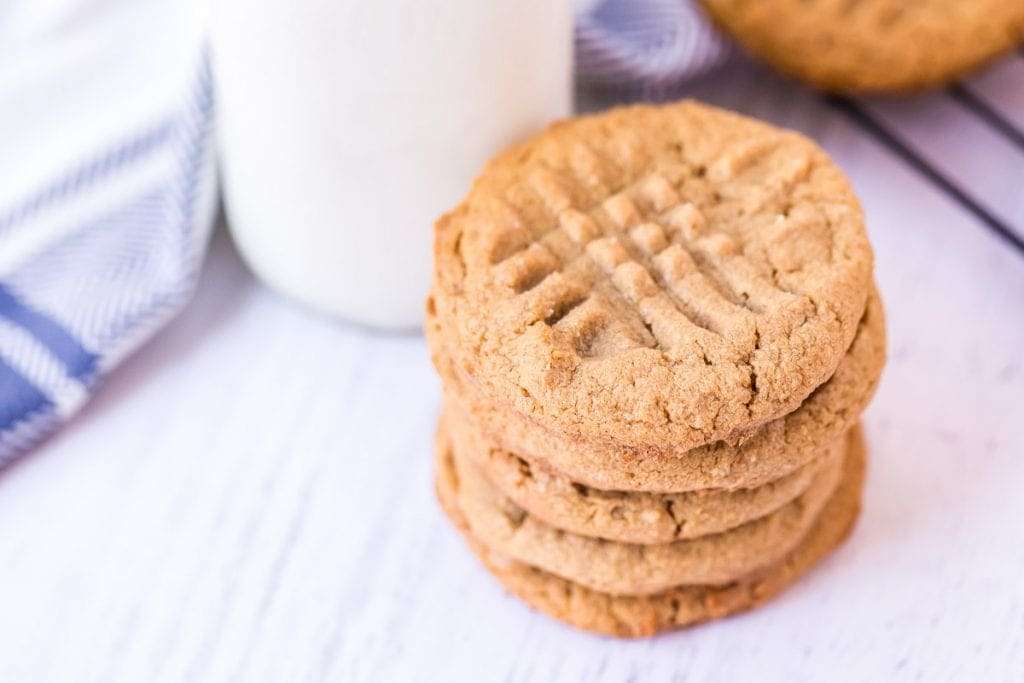 White background with a stack of cookies and jar of milk in background with blue and white napkin