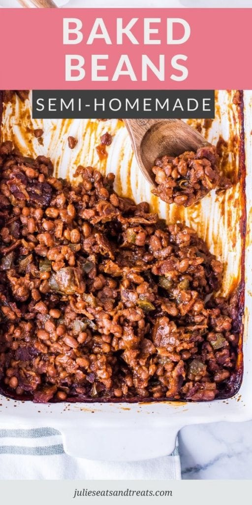 Baked beans in a white casserole dish with a wooden spoon scooping them out