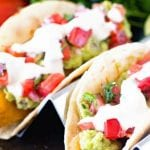 Fish Tacos topped with guacamole, tomatoes, and sour cream