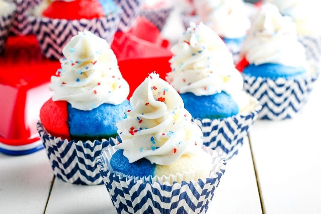 Multiple 4th of July Cupcakes with red white and blue cake in a chevron blue and white cupcake liner and white frosting with sprinkles on a white background
