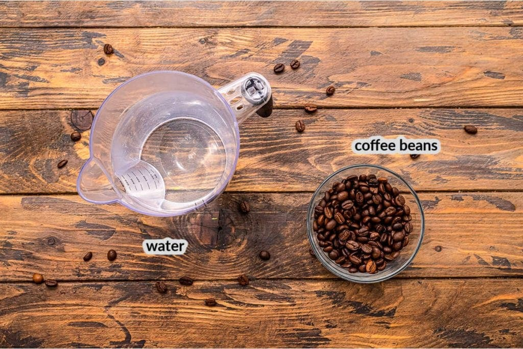 Wooden background with water in a measuring cup and coffee beans in a glass bowl