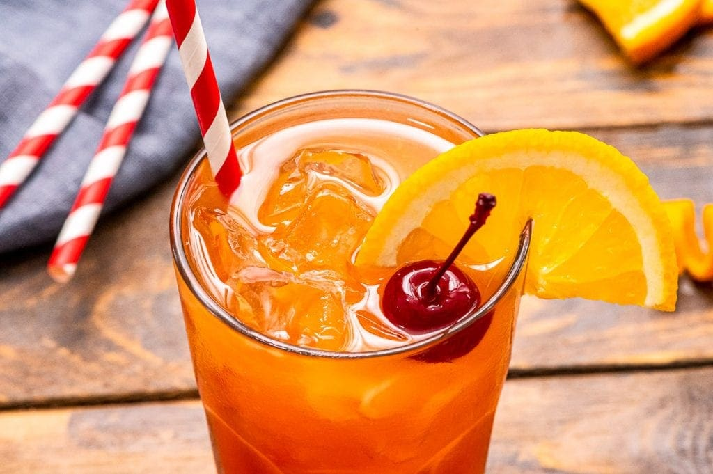 wood background with mixed cocktail garnished with cherry and orange slice and ride striped straw