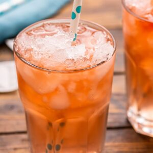 Glass with crushed ice and arnold palmer in it with a blue polka a dot straw