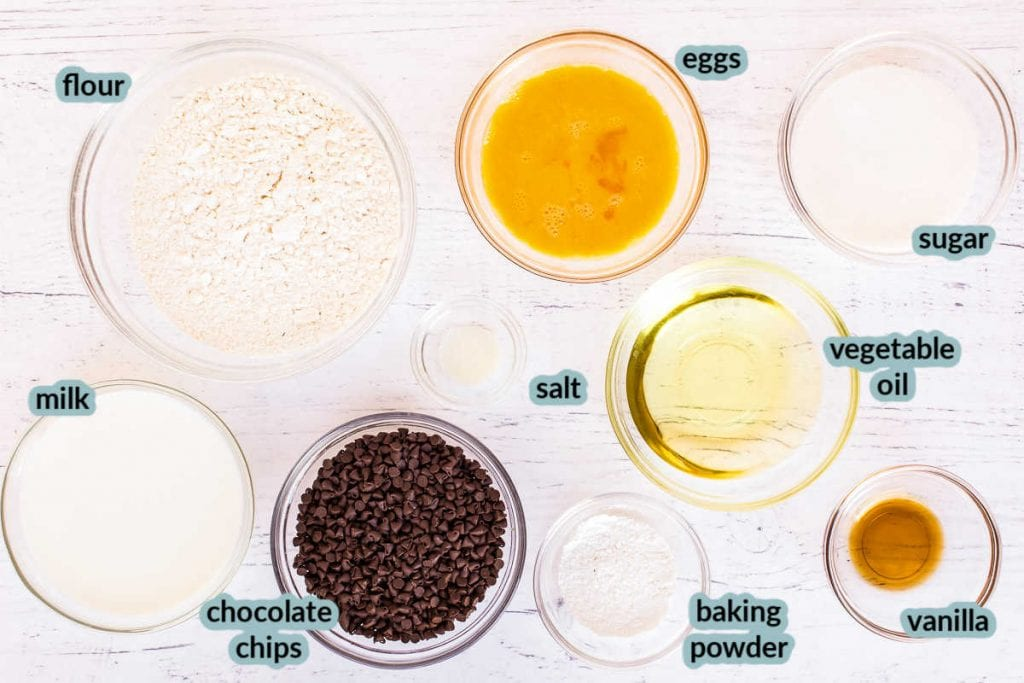 Ingredients for muffins in clear bowls on white background like flour sugar eggs chocoalte chips and more