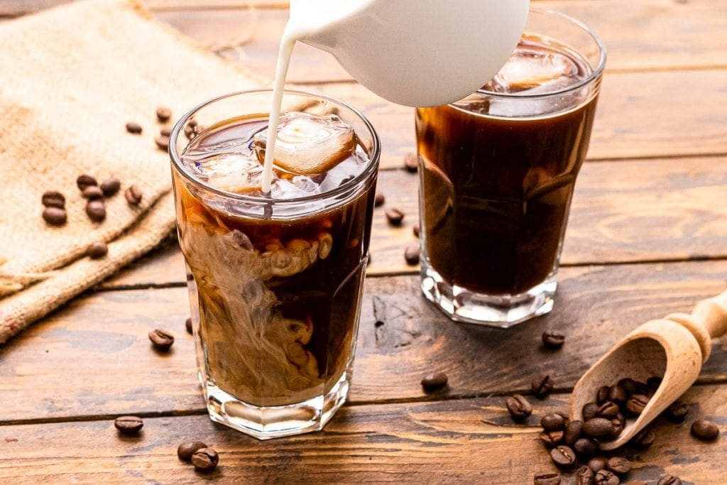 White pitcher pouring milk into a cold brew coffee in glass. Another glass of coffee behind that one on. On a wooden background with coffee beans on it.