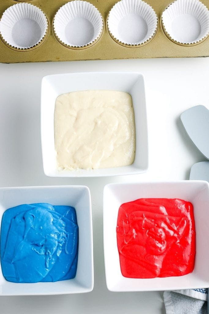 Overhead image with three square bowls one with white cake mix, one with red cake mix and one with blue cake mix. Muffin pan with white liners in it behind that.
