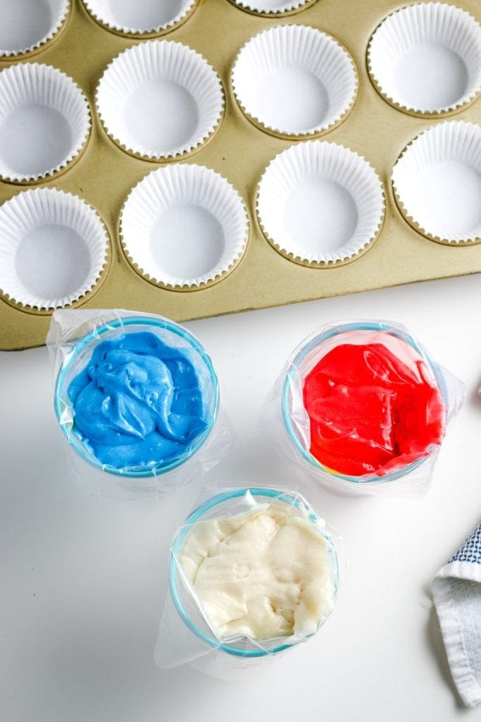 Overhead image cups holding bags of red, white and blue cake mix and muffin pan with white liners behind it.