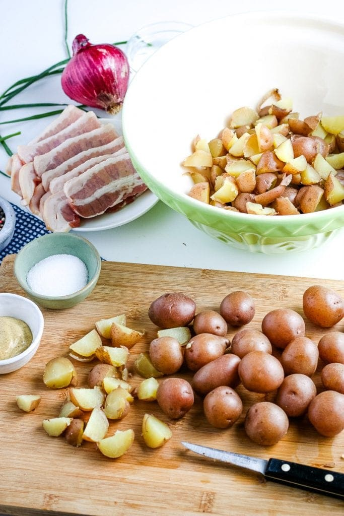 Cutting board with cooked red potatoes being cut into pieces