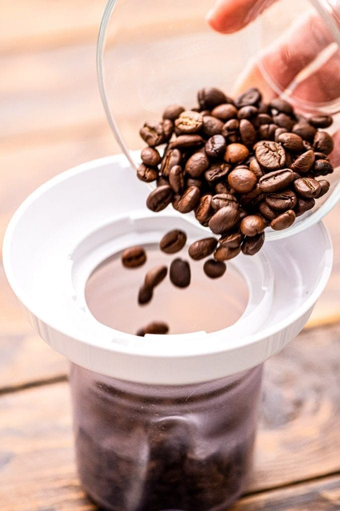 Coffee beans being poured into a coffee grinder with a white top