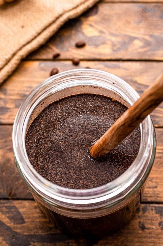 Wooden spoon stiring water and coffee grounds together in glass jar.