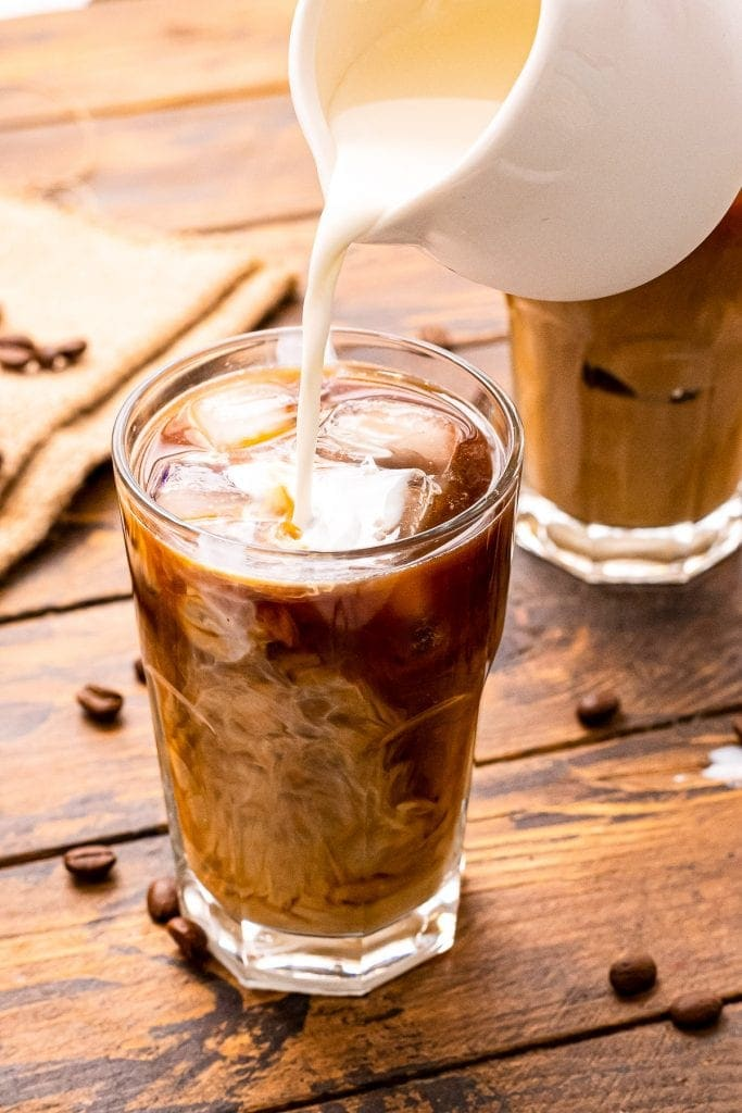 White pitcher pouring milk into a glass of cold brew coffee that's on a wooden background with coffee beans on it.