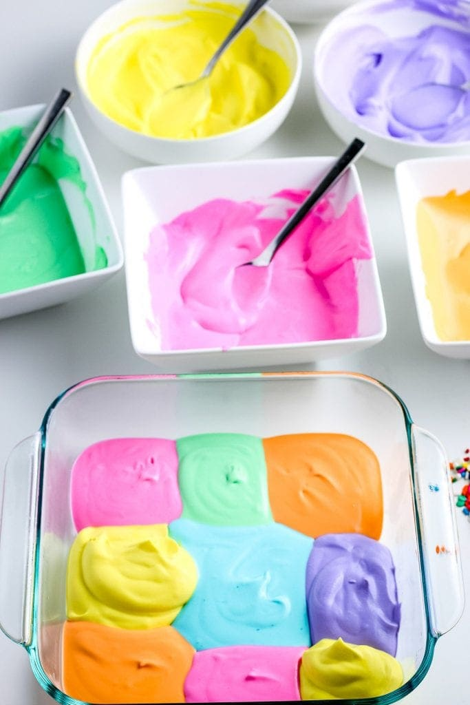 Glass baking dish with squares of different colors of ice cream and bowls of mixture behind it.