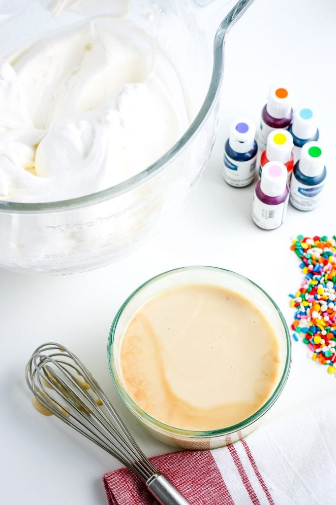 Glass bowl with sweetened condensed milk and vanilla mixed together, whipped cream in glass bowl behind it and food coloring containters.