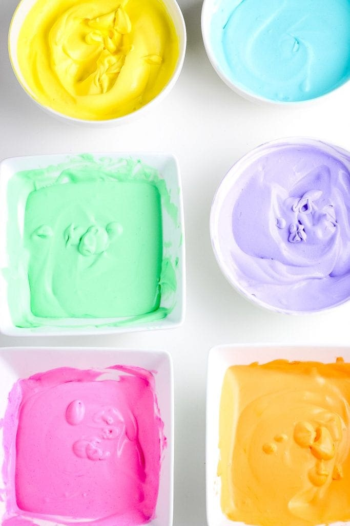 Six white bowls with mixed ice cream for rainbow ice cream in it. Bowls each container pink, orange, purple, green, blue and yellow.