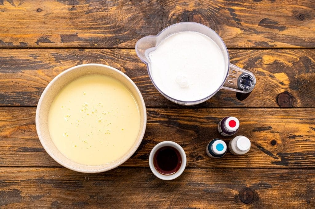 Bowl with sweetened condensed milk, vanilla and whipping cream also food coloring bottles of red, white and blue.