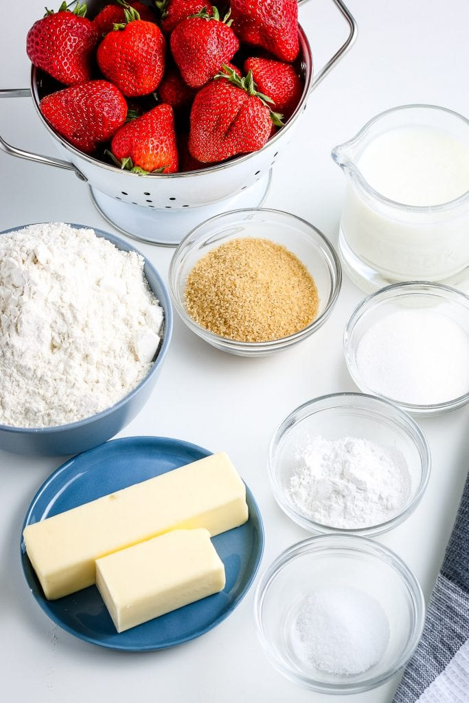 Ingredients needed to make Strawberry Shortcake in glass bowls and plates. Ingredients include butter, sugar, flour, strawberries, brown sugar, salt, milk and more.