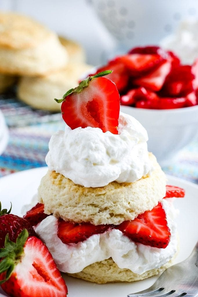 A strawberry shortcake on white plate with strawberries in background and biscuits.
