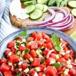Portrait photo of watermelon salad in blue bowl with red onion, cucumber, feta cheese in background