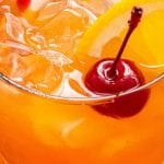 Alabama Slammer in glass with an orange slice and a cherry