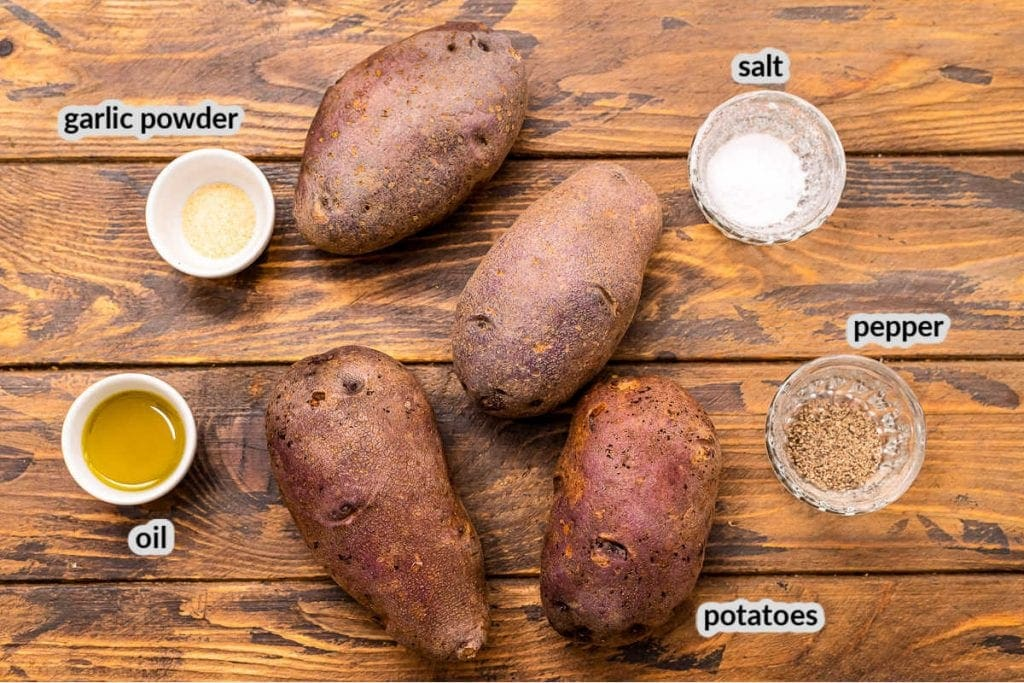 Overhead image showing wooden background with ingredients to make baked potatoes including salt, pepper, oil, garlic powder and potatoes