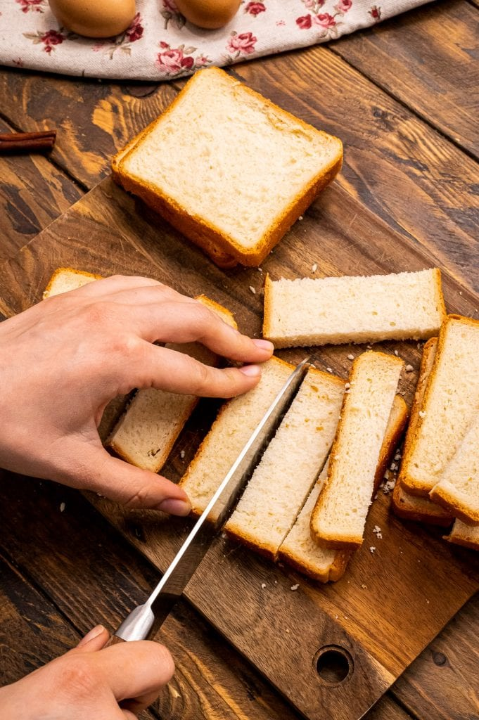 hand holding slice of bread and other hand holding knife slice bread into strips