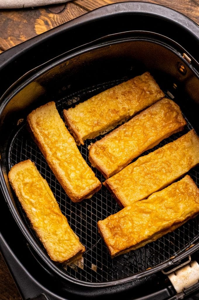 Air Fryer Basket with cooked french toast sticks in it.