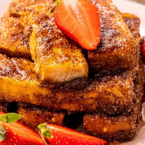 Close up of Air Fryer French Toast sticks topped with a sliced strawberry and more sliced strawberries next to it on the plate