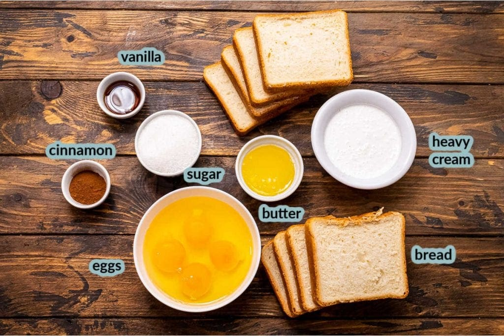 Ingredients for French Toast Sticks on a wood background including bread slices along with bowls of eggs butter sugar vanilla cinnamon