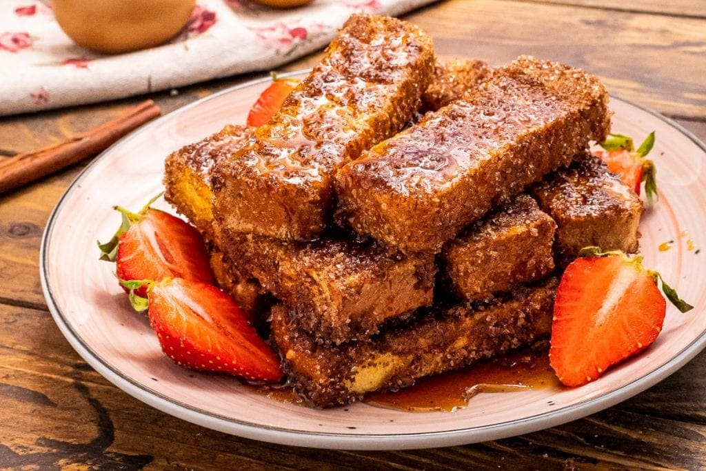 White Plate with French Toast sticks on it along with sliced strawberries beside it on a wood background