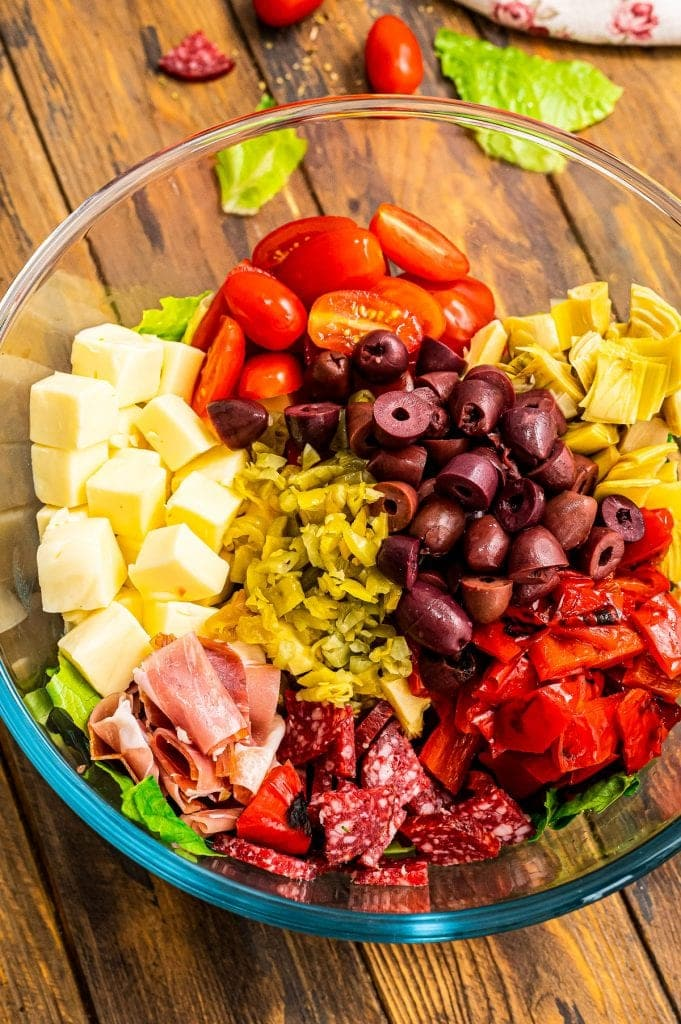 Salad ingredients in glass bowl for Antipasto salad before mixing.