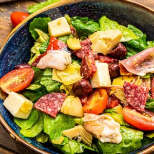 Portrait photo of a dark blue ceramic bowl with tossed Antipasto Salad in it on a wooden background