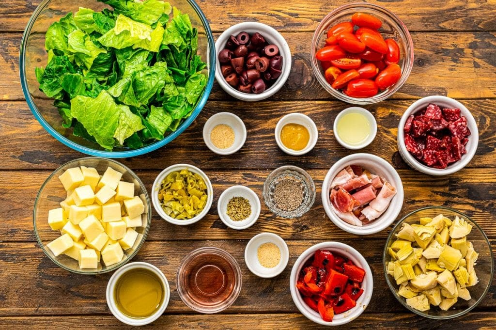 Overhead image of ingredients for Antipasto Salad in bowls.