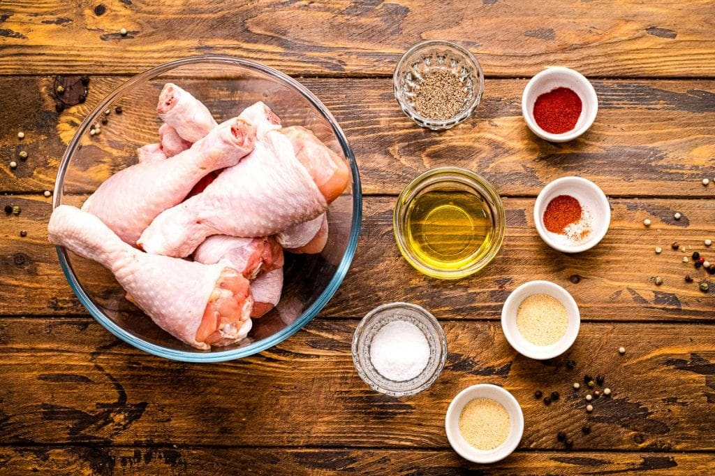 Overhead image of ingredients for baked chicken legs in glass bowls including chicken legs, oil, and seasonings.