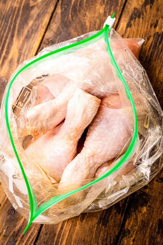 Resealable gallon bag with raw chicken drumsticks in it.