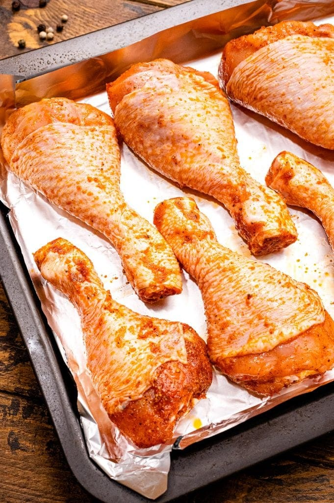 Raw chicken legs that are seasoned with seasonings and laying on aluminum foil lined baking sheet.