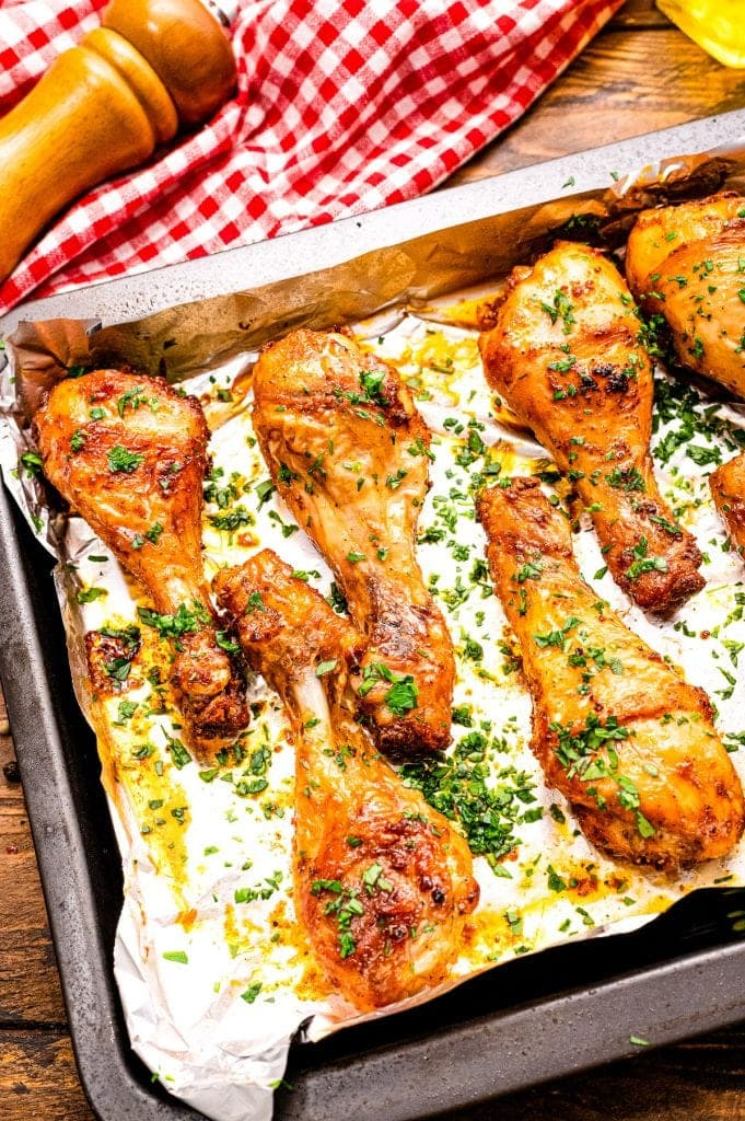 Baked Chicken Legs on an aluminum foil lined pan after baking and garnished with chopped parsley.