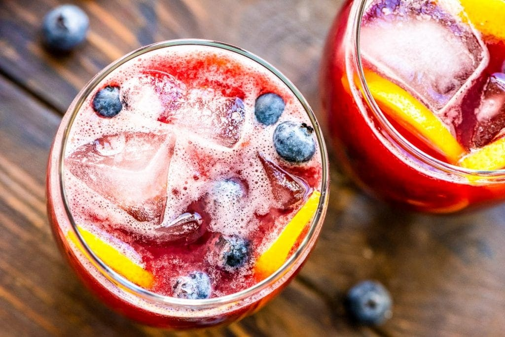 Overhead image of two glasses of fresh blueberry lemonade garnished with blueberries and lemon slices