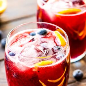 Two glasses on wooden background of freshly made blueberry lemonade with ice, blueberries, and lemon slices in glasses.