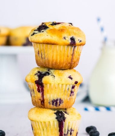 Stack of three blueberry muffins with blueberries beside them