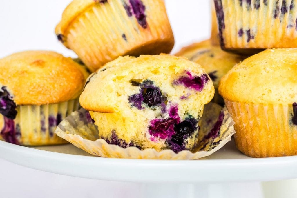 Blueberry muffin that is unwrapped and bite gone sitting on the wrapper with more muffins next to it