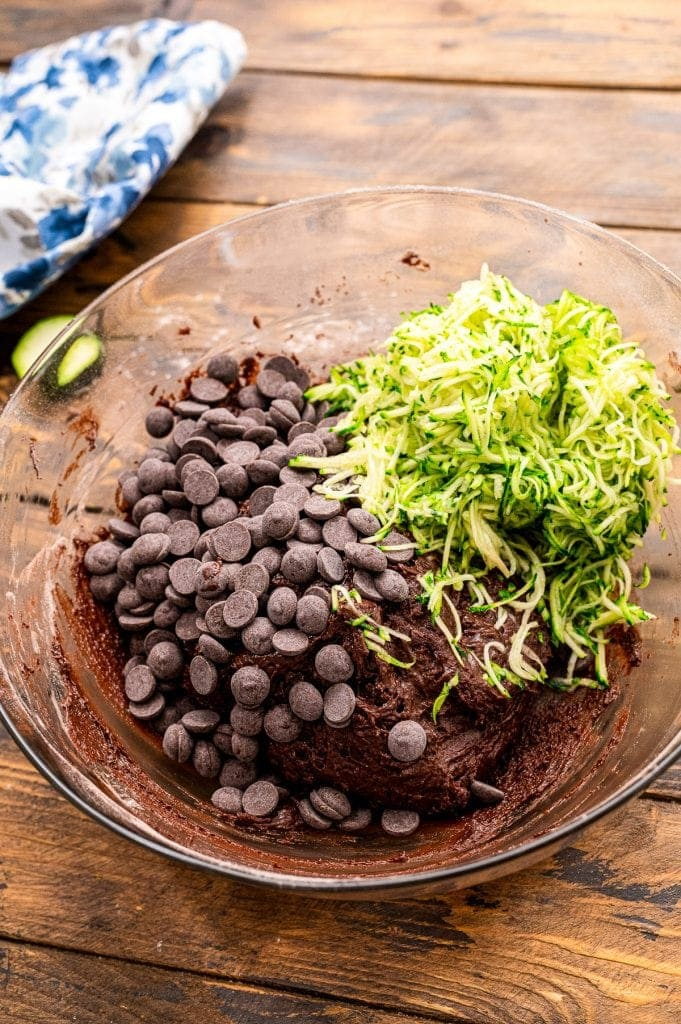 Batter mixed in bowl with chocolate chips and shredded zucchini on top.