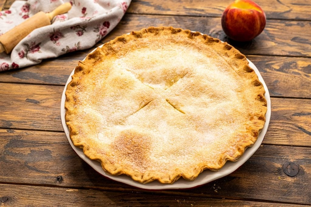 Double Crust Peach Pie Baked in pie dish on wooden background